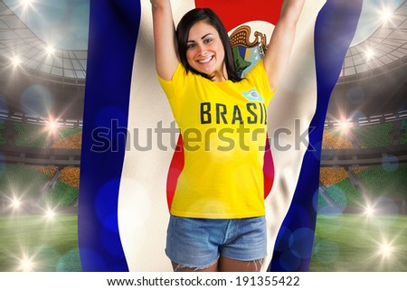 Excited football fan in brasil tshirt holding costa rica flag against large football stadium with brasilian fans