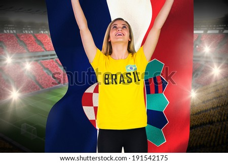 Excited football fan in brasil tshirt holding croatia flag against vast football stadium with fans in yellow and red