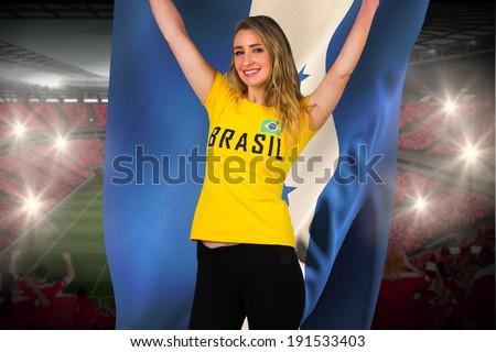 Excited football fan in brasil tshirt holding honduras flag against vast football stadium with fans in red