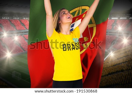 Excited football fan in brasil tshirt holding portugal flag against vast football stadium with fans in yellow and red