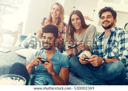 Excited friends playing video games at home.