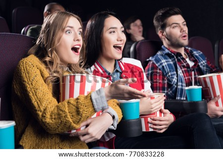 excited friends with popcorn and soda watching movie in cinema