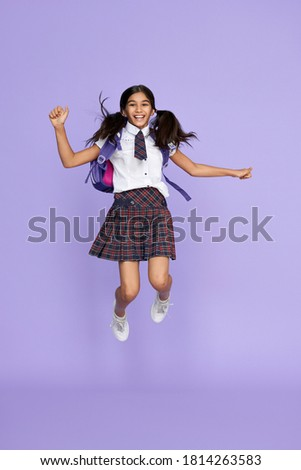Excited funny indian kid primary school girl with backpack bag wearing uniform jumping flying up isolated on violet background. Happy crazy latin child schoolgirl student feeling freedom having fun.