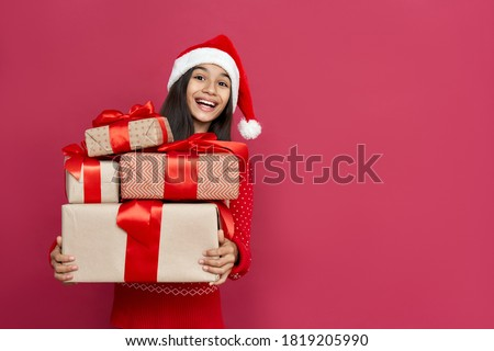 Excited funny indian latin kid child girl wears santa hat looking at camera holding many gifts boxes celebrating happy 2021 New Year isolated on red background. Merry Christmas presents shopping sale. Photo stock ©