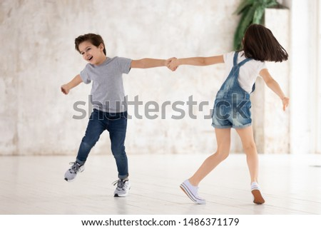Photo of Excited funny little cute kids siblings playing active game at home, two happy small children boy and girl holding hands running spinning around laughing in living room in new modern empty apartment