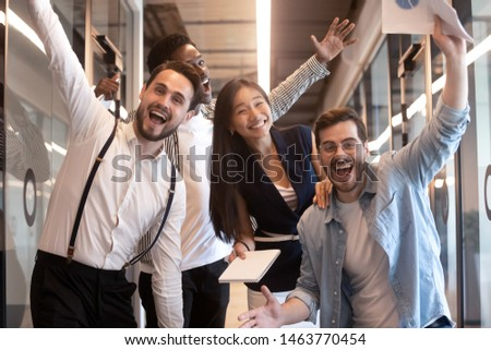 Excited funny multiethnic staff people business team stand in office looking at camera, happy diverse professional colleagues group celebrate success win victory reward at corporate party, portrait