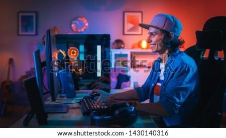Excited Gamer Playing First-Person Shooter Online Video Game on His Personal Computer. Room and PC have Colorful Neon Led Lights. Young Man is Wearing a Cap. Cozy Evening at Home.