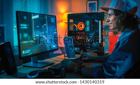 Excited Gamer Playing First-Person Shooter Online Video Game on His Powerful Personal Computer. Room and PC have Colorful Neon Led Lights. Young Man is Wearing a Cap. Cozy Evening at Home.