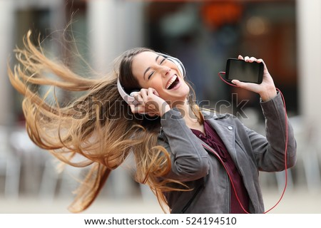 Excited girl dancing and listening music with headphones and smart phone in the street with hair moving #524194510