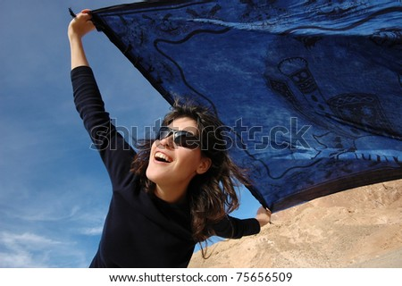 Excited girl dancing with a blue shawl on a windy day.