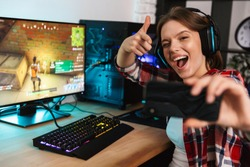 Excited girl gamer sitting at the table, playing online games on a computer indoors, taking a selfie