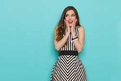 Excited girl in black and white striped dress holding head in hands, shouting and looking away. Three quarter length studio shot on turquoise background.