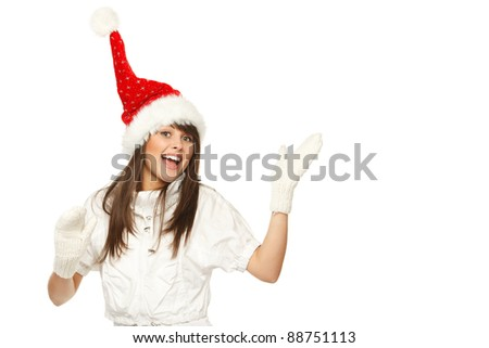 Excited girl in Santa hat showing empty copy space, over white background