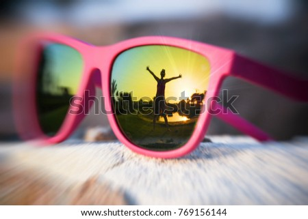 Excited girl with hands wide opened silhouette in the pink sunglasses reflection on a summer day and sunset