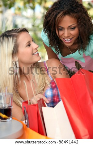 Excited girls watching their shopping bags