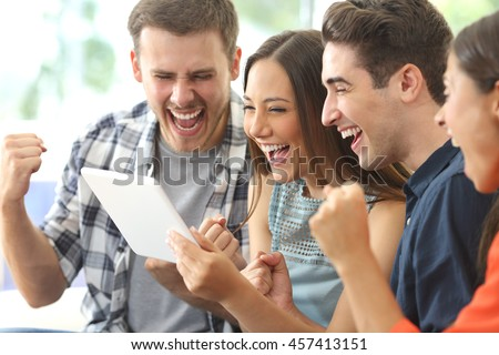 Excited group of four friends viewing media content on line from a tablet in a house interior