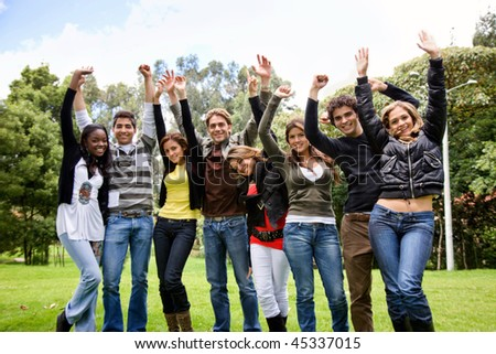 Excited group of people smiling with their arms up