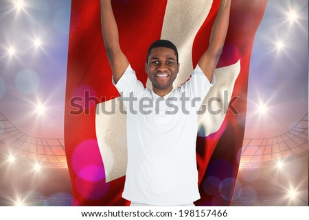Excited handsome football fan cheering holding swiss flag against large football stadium under purple sky