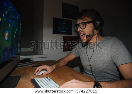 Excited handsome young gamer in glasses and earphones playing computer game and shouting at home