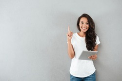 Excited happy asian woman holding tablet computer and pointing finger up at copy space while standing isolated over gray background