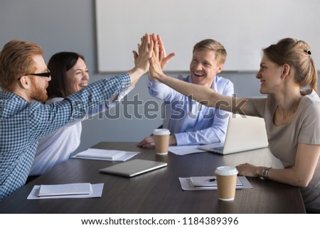 Excited happy business team of employees or partners group giving high five during meeting celebrating corporate success, promising support, engagement and loyalty, good relations, unity concept