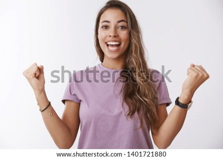 Excited happy charming smiling woman, tanned curly hair, clenching fists joyfully celebrating accomplishment, victory successful cheer, hooray, joyful win, standing amused white background #1401721880