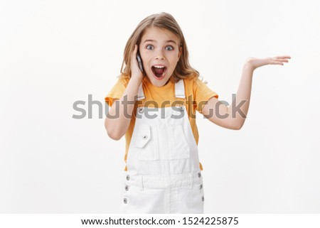 Excited happy cute little girl hearing pleasant awesome news via smartphone, raise hand up excitement and overjoy, hold mobile phone near ear, open mouth thrilled, react emotive, white background