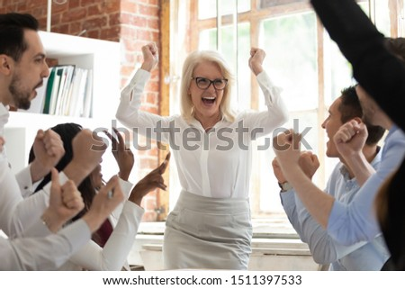 Excited happy diverse staff in spotlight overjoyed middle-aged woman team leader screaming with joy, department celebrating business success make great deal, fantastic results, growth of sales concept Сток-фото ©