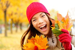 Excited happy fall woman smiling joyful and blissful holding autumn leaves outside in colorful fall forest. Beautiful energetic mixed race Caucasian / Asian Chinese young woman.