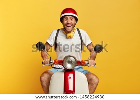 Excited happy male courier glad to receive bonus for punctuality, stares with eyes full of happiness, drives motorbike, wears protective headgear, isolated on yellow background, travels alone