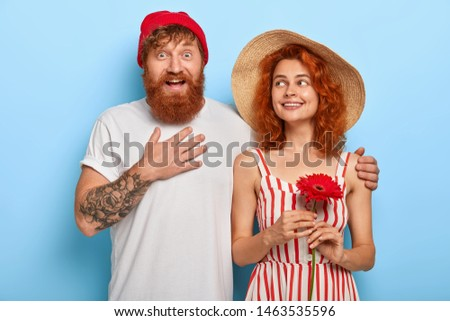 Excited happy man touches chest, impressed by good news, embraces girlfriend who holds red gerbera, have walk together, meet friends, isolated on blue wall. People, relationship, love concept