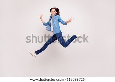 Excited happy pretty  girl in casual jeans clothes high jump with raised hands and legs, on white background