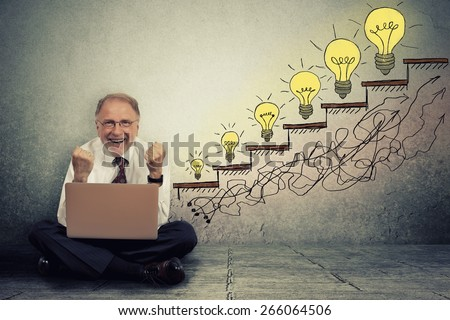 Excited happy senior executive man working on computer sitting on a floor in his office celebrates business success, promotion, company growth isolated on gray wall texture background