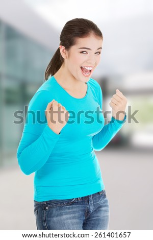 Excited happy success young woman with fists up.