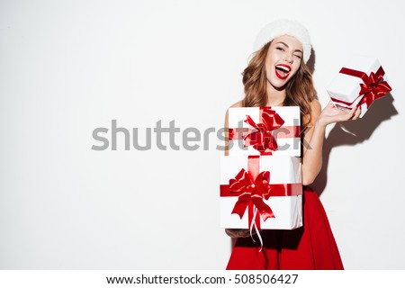 Excited happy woman in red santa claus outfit holding stack presents isolated on the white background stock photo
