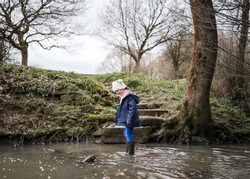 Excited happy young girl cute in wellington boots walking autumn countryside in river stream splashing in water exploring the great outdoors nature park with bobble hat and blue coat in winter nature