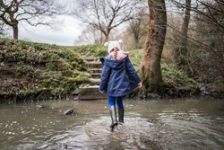 Excited happy young girl in wellington boots walking through autumn countryside river stream splashing in water exploring the great outdoors nature park with bobble hat and blue coat in winter flowing