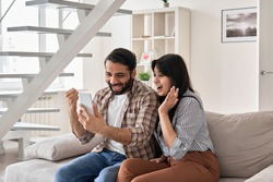 Excited happy young indian family couple winners look at smart phone celebrate win, success, watching game, winning online lottery, reading great news, get shopping discount in mobile message at home.