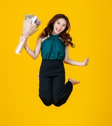 Excited in love Asian female brunette holding a flower bouquet high jumps into the air with cheerful and very happy. Freeze stop action with studio shot isolated on bright yellow background