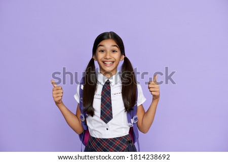 Excited indian kid primary school girl with backpack wearing uniform showing thumbs up isolated on violet background. Happy latin child student celebrating freedom, recommending best education choice. Photo stock ©