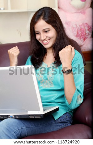 Excited Indian woman working with laptop sitting on sofa