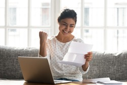 Excited indian young woman sit at home couch feel euphoric read good news in post letter, happy ethnic millennial girl receive pleasant notice in postal correspondence, reward, success concept