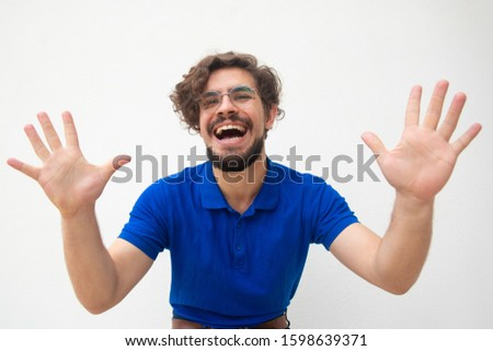 Excited joyful crazy guy touching air, showing palms, laughing. Handsome bearded young man in blue casual t-shirt posing isolated over white background. Fun or joy concept