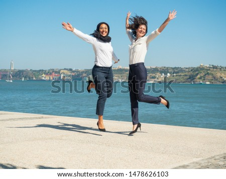 Excited joyful female business colleagues enjoying team success. Businesswomen in office clothes and hijab laughing, shouting for joy, dancing and having fun outside. Successful concept