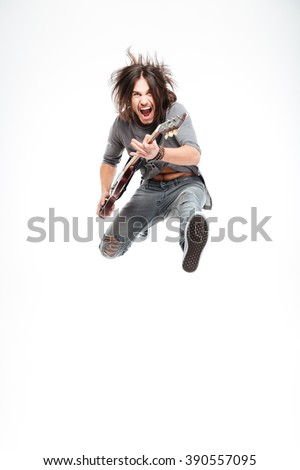 Excited joyful young male guitarist with electric guitar shouting and jumping over white background #390557095