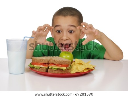 Excited kid ready to eat a healthy sandwich meal, meat sandwich on whole wheat bread, tortilla chips, and a green apple