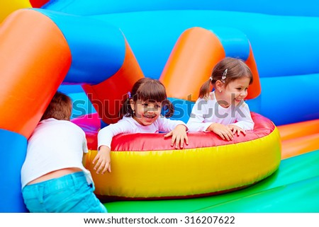 excited kids having fun on inflatable attraction playground #316207622