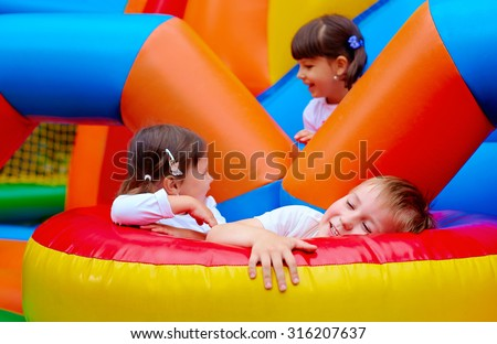 excited kids having fun on inflatable attraction playground #316207637