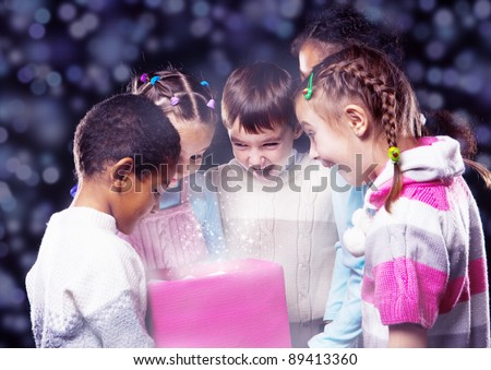 Excited kids looking into shining Christmas box
