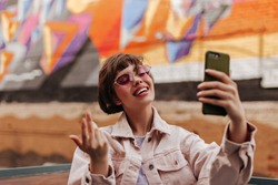 Excited lady with short hair taking photo outdoors. Brunette teen girl in light jacket and pink glasses making selfie and smiling in city..